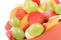 Fruity salad. Bowl of fruity salad - banana strawberry nectarine and grape - isolated on white Royalty Free Stock Images
