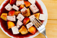 Fruity salad with cheese in red wine. On wooden desks close-up Stock Photography