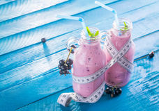 Fruity smoothie with black currant. On blue background royalty free stock image