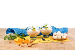 Fruity smoothies in dessert glasses isolated on a white background. Cocktails next to Turkish delight and dried apricots Royalty Free Stock Photography