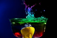 Fruity Splash. Colorful high speed photo of a lemon splashing in colored water Stock Image
