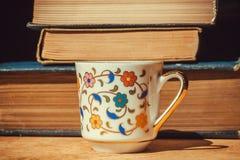 Frukost av bokmalen med tappningböcker och koppen kaffe för blom- design Selektivt fokusera Royaltyfri Fotografi