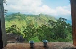 Frukost av ett par med kaffekoppar på den gröna kullen under blå himmel Romantiskt landskap med berg Arkivbilder