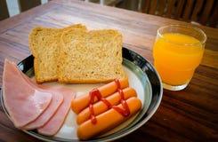 Frukost av skinka, exponeringsglas amerikansk frukost av för orange fruktsaft och rostat brödför närbilden Royaltyfri Fotografi