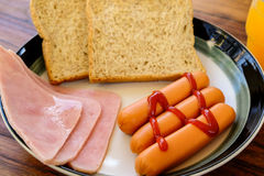 Frukost av skinka, exponeringsglas amerikansk frukost av för orange fruktsaft och rostat brödför närbilden Arkivbild
