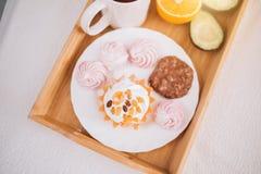 Frukost för bra morgon i säng med te, apelsin, avokado, kaka, marshmallower, chokladkex i trämagasin livsstil mat, royaltyfri foto