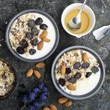 Frukost från sunda säsongsbetonade ingredienser: granola flingor, honung, mörka druvor, mandlar i en portiongrå färg som är pial  arkivfoton