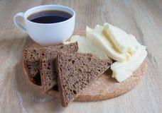 Frukost: getost och kopp kaffe och skivor av rågbröd Skivor av keso på en beige bakgrund Arkivbild