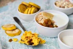 Frukost: hemlagad granola, banan, nya bär, yoghurt på ljus textilbakgrund Begreppet av sunt äta, hög-kol Arkivfoton