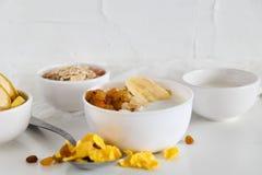 Frukost i den glass koppen: hemlagad granola, banan, nya bär, yoghurt på vit bakgrund Begreppet av sunt äta som är högt-c Fotografering för Bildbyråer