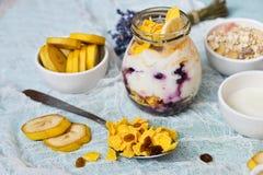 Frukost i en glass krus: hemlagad granola, banan, nya bär, yoghurt på en ljus textilbakgrund med en bukett av lavendel Fotografering för Bildbyråer
