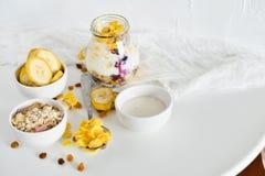 Frukost i en krus: cornflakes banan, nya bär, granola, yoghurt på en ljus bakgrund Begreppet av sunt äta som är högt Royaltyfri Fotografi