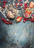 Frukost i krus Havremjöl med jordgubbar och annat nytt bär, muttrar och frö på lantlig bakgrund, bästa sikt royaltyfria foton