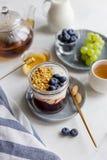 Frukost i krus med granola, yoghurt, driftstopp och bär royaltyfri fotografi