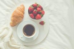 Frukost i säng giffel, kopp av coffe och ny jordgubbe Arkivfoto