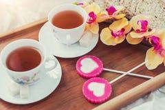 Frukost i säng i valentindag Kopp te och söta godisar Förälskelse- eller feriebegrepp Arkivfoto