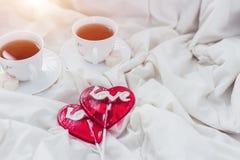 Frukost i säng i valentindag Kopp te och söta godisar Förälskelse- eller feriebegrepp Royaltyfri Bild