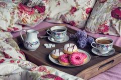 Frukost i säng med kaffe och donuts fotografering för bildbyråer