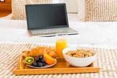 Frukost i säng och en bärbar dator Arkivfoto