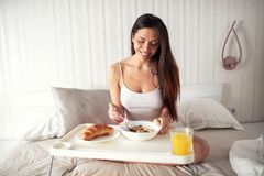 Frukost i säng, sädesslag, bakat gods och orange fruktsaft arkivfoton