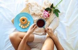 Frukost i sängen Kvinna som hemma dricker kaffe i hennes säng, medan kontrollera hennes bärbar dator royaltyfri bild