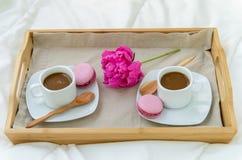 Frukost i s?ng f?r tv? Tr?magasin med kaffe, makron och Bizet arkivbild