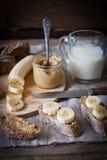Frukost - jordnötsmör, banan, mjölkar Arkivbilder