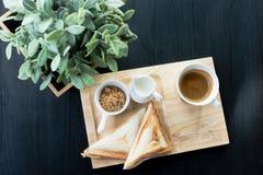 Frukost - kaffe, mjölkar, farin och rostat bröd med sidor på svart bakgrund Royaltyfria Bilder