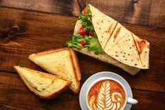 Frukost med cappuccino och smörgåsen Arkivfoto