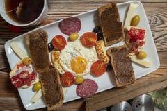 Frukost med det stekte ägget, rågbröd, granatäpplet, carobdeg, ostar, oliv, torr salami, tomater och te royaltyfria bilder