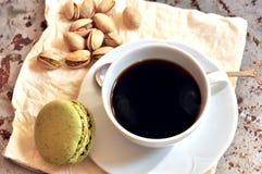 Frukost med pistacchiomaccarons och kaffe Arkivbild