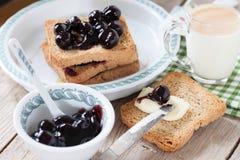Frukost med sura Cherry Jam Milk And Rusks Arkivbilder