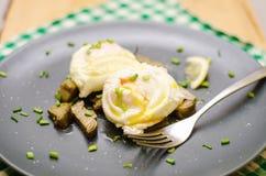 Frukost med tjuvjagade ägg och kronärtskockor Arkivbild