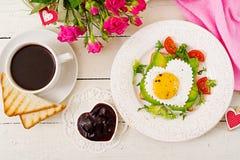 Frukost på dag för valentin` s - smörgås av det stekte ägget i formen av en hjärta, en avokado och nya grönsaker Arkivbilder