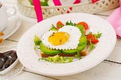 Frukost på dag för valentin` s - smörgås av det stekte ägget i formen av en hjärta, en avokado och nya grönsaker Arkivbild