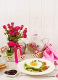 Frukost på dag för valentin` s - smörgås av det stekte ägget i formen av en hjärta, en avokado och nya grönsaker Royaltyfri Foto