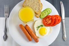 Frukost på en vit platta på ett svartvit tabell stekt ägg i enformad stekt korv, nya grönsaker Royaltyfria Foton