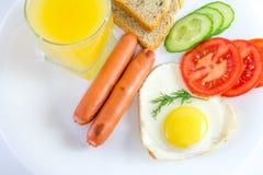Frukost på en vit platta, stekt ägg i enformad stekt korv, nya grönsaker, fruktsaft, s Fotografering för Bildbyråer