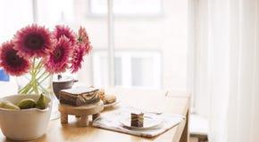 Frukost på tabellen vid fönstret En bukett av blommor och kaffe den antika koppen för affärskaffeavtalet danade för pennplatsen f arkivbilder