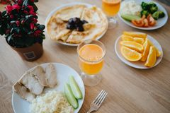 Frukost på trätabellen Pannkakor apelsiner, ny orange fruktsaft, gurkan, tomaten, ris, broccoli, kött, blommar Arkivbilder