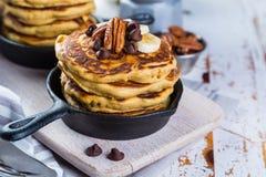 Frukost - pannkakor för chokladchip med kaffe och fruktsaft arkivfoton