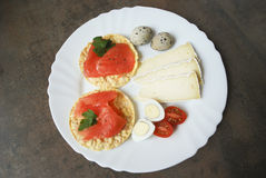 Frukost: rissmällare med laxen, vaktelägg, ost, tomater Royaltyfri Foto