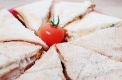 Frukost: smörgåsar med ost och skinka som dekoreras med körsbärsröda tomater Fotografering för Bildbyråer