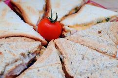 Frukost: smörgåsar med ost och skinka som dekoreras med körsbärsröda tomater Arkivbild