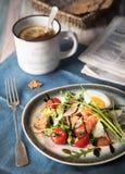 FrukostArugulasallad med laxen och parmesan, en kopp te med citronen Lantlig stil Matfoto royaltyfri fotografi