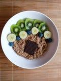 Frukostbunke med bananen, kiwin, blåbäret, mysli och mörk choklad från över royaltyfria foton