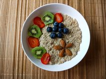 Frukostbunke med jordgubbar, kiwi och blåbär, med sädesslag och mandlar som bildar en blomma royaltyfri fotografi