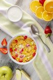 Frukostcornflakens och jordgubbar med mjölkar, yoghurten och orange fruktsaft royaltyfri foto