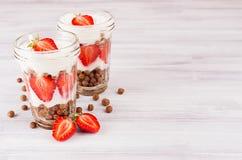 Frukosten med choklad klumpa ihop sig havreflingor, skivad jordgubbe i krus på det vita wood brädet Dekorativ gräns med kopiering Royaltyfri Foto