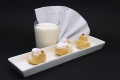 Frukosten mjölkar och eclairkakan på en svart bakgrund royaltyfria bilder